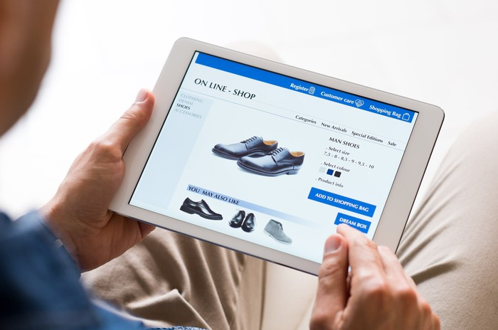 A man uses a tablet to shop online for shoes.
