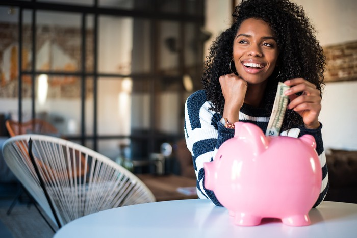 Young woman putting dollar bill into a piggy bank