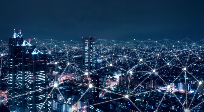 A network of interconnected dots over a nighttime cityscape.