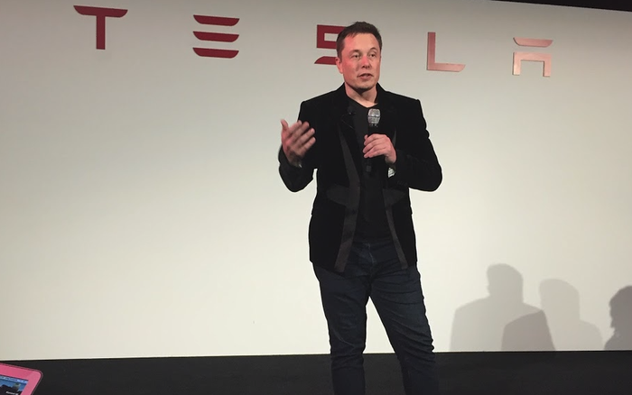 Tesla CEO Elon Musk standing on a stage holding a microphone, in front of a backdrop with a Tesla logo on it.