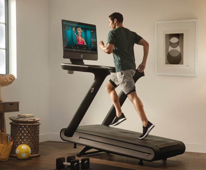 A man is walking on a Peloton treadmill while watching a fitness class.
