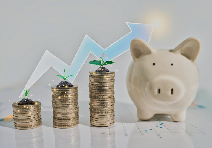 Progressively taller stacks of coins with sprouts on top on each, representing a rising stock chart, sit in front of an upward-trending arrow and next to a piggy bank.