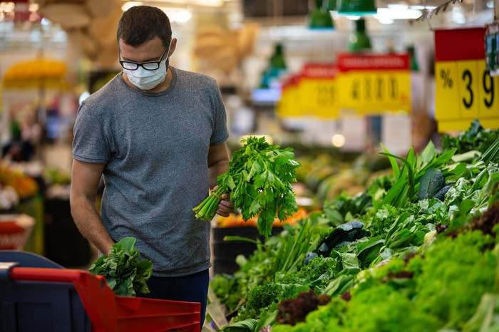 A young male adult shops for vegetables while wearing a face mask.