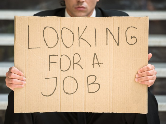 A businessman in a suit holding up a cardboard sign that reads, Looking for a job.