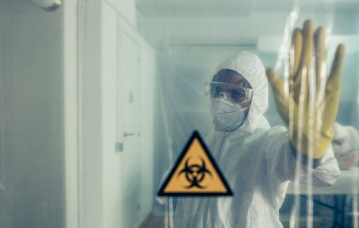 Scientist in hazmat suit in sealed-off area with biohazard sign