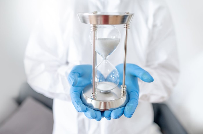 Scientist holding an hourglass with gloved hands