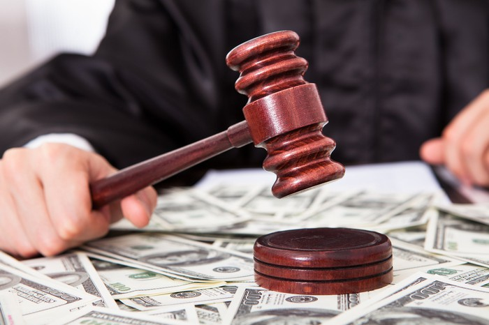Judge holding a gavel over a pile of $100 bills