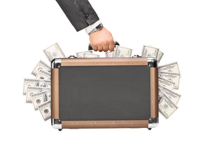 Hand holding briefcase with $100 bills sticking out