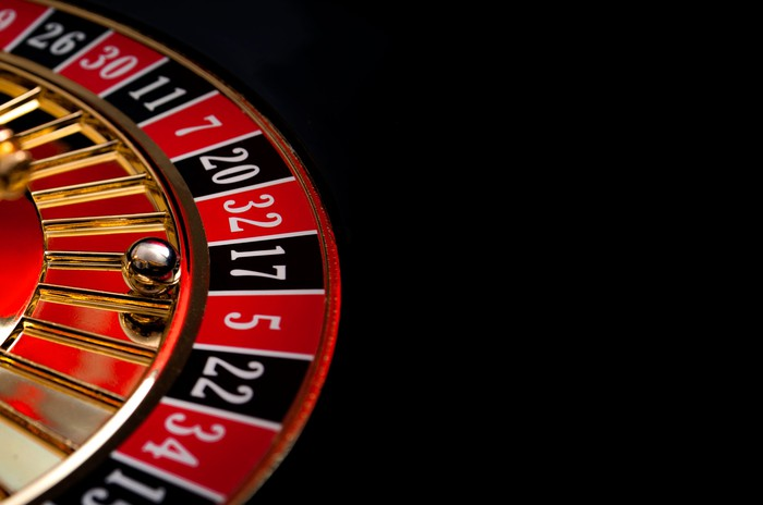 A roulette wheel with a black background.