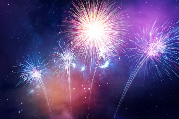 A fireworks display in purple tones is shown against a night sky.