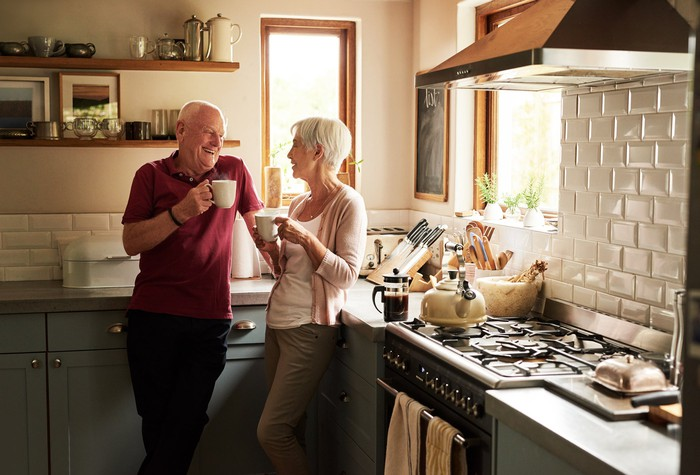 Senior couple standing in the kitchen drinking from white mugs.