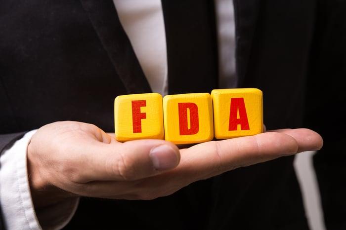 Businessman holding blocks spelling FDA