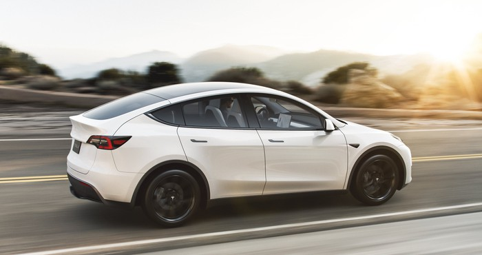 A white Tesla Model Y, an upscale electric crossover SUV.