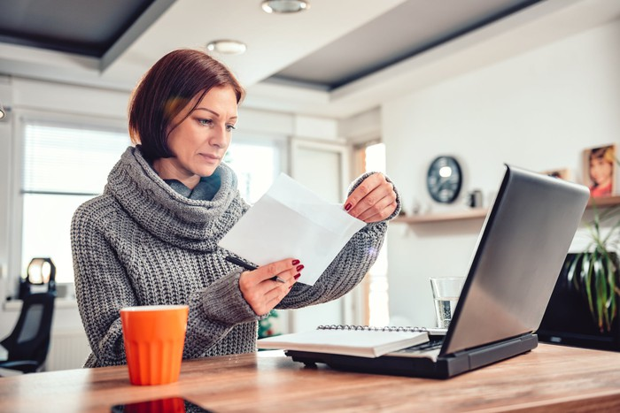 Woman at laptop opening letter