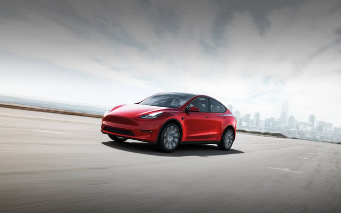 Red Tesla Model Y on a road, with a city skyline in the distant background.
