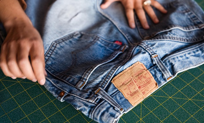 A pair of Levi's jeans lying on a tailor's cutting mat.