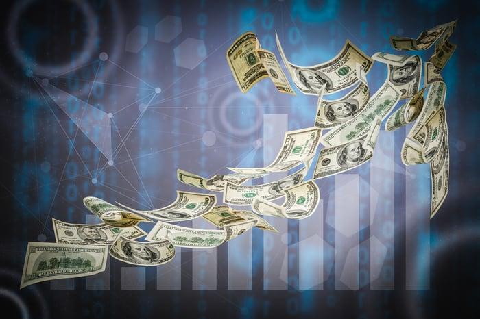 Upward arrow made up of fluttering $50 and $100 bills.