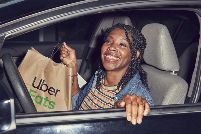 A woman in a car holding a bag that says Uber Eats
