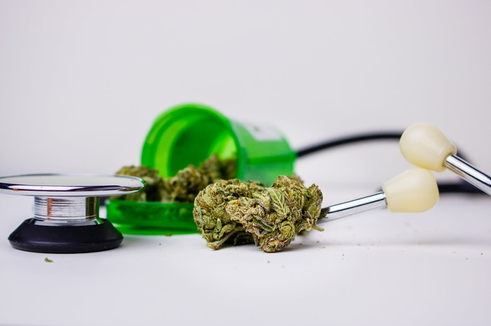 Cannabis flower spilling from a pill bottle next to a stethoscope.