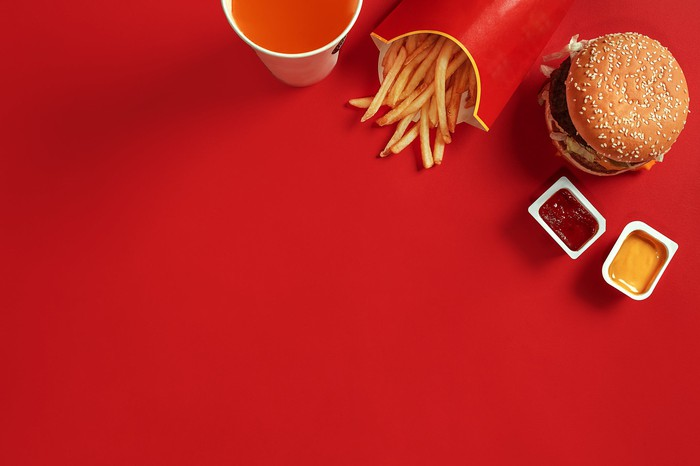 A burger, fries, a drink, and two dipping sauces sitting on a red table.