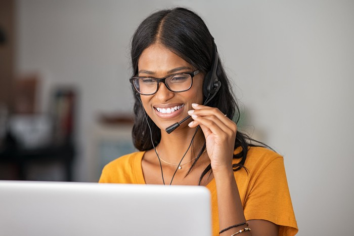 Young woman wearing a headset while serving a customer remotely.