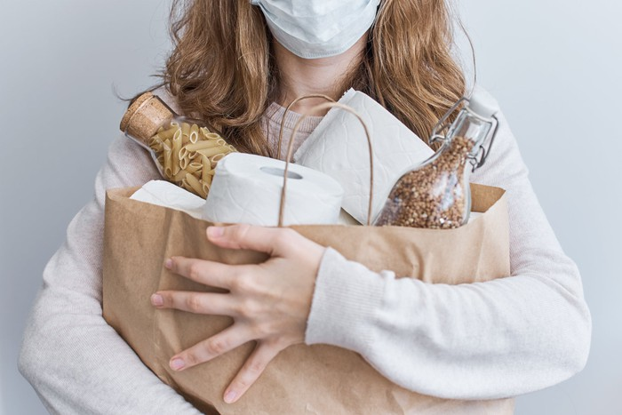 A woman in a face mask clutches a grocery bag full of toilet paper rolls and bottles of pasta and grains.