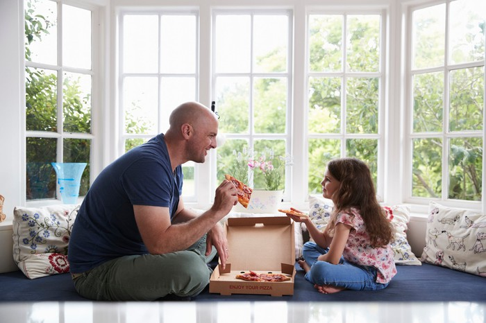 Father and daughter sitting on a window seat and eating pizza out of a box.