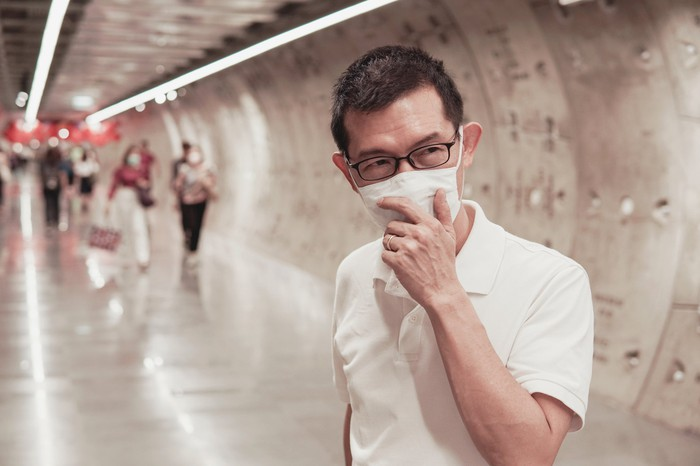 A man holding a mask to his face on a subway tunnel platform.