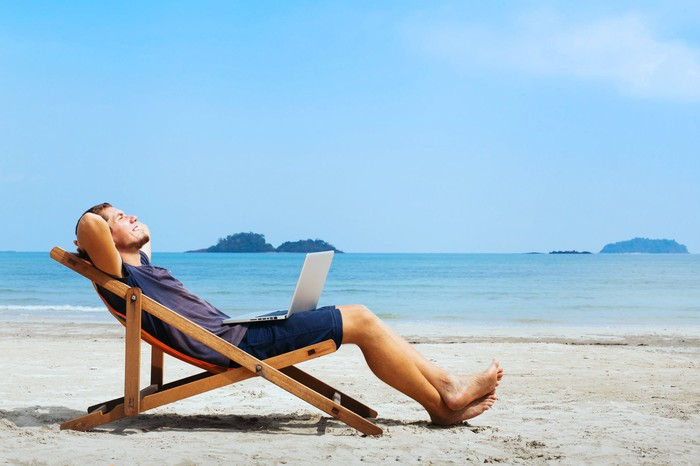 An investor relaxes on the beach with a laptop in his lap.
