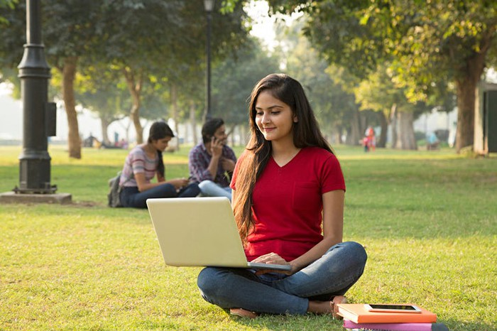 A young woman sitting on the ground uses her laptop.