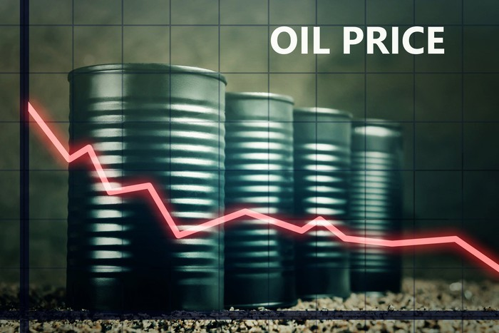 A price chart heading lower with oil barrels in the background.