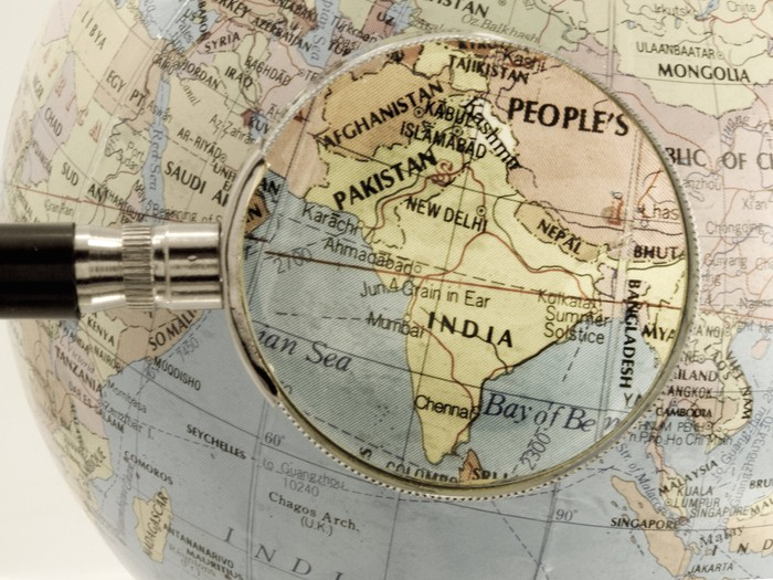 Magnifying glass held over a map of India.