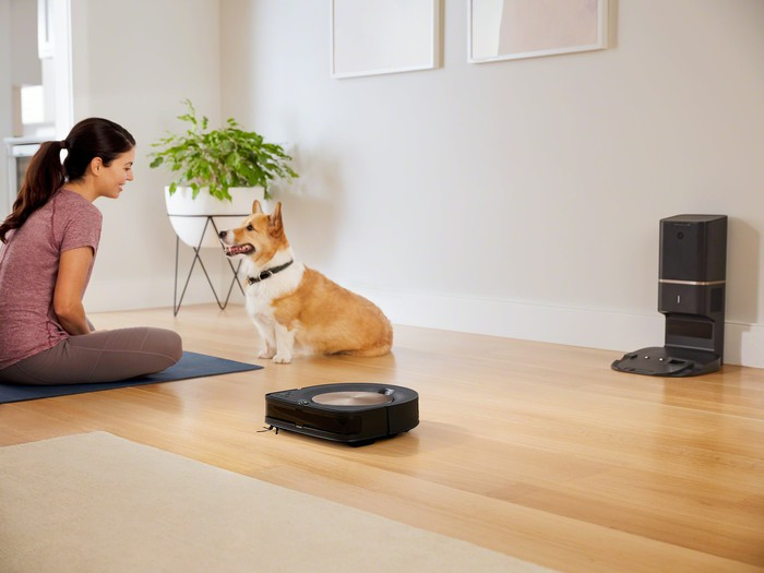 A Roomba cleaning the floor with a woman and dog sitting nearby