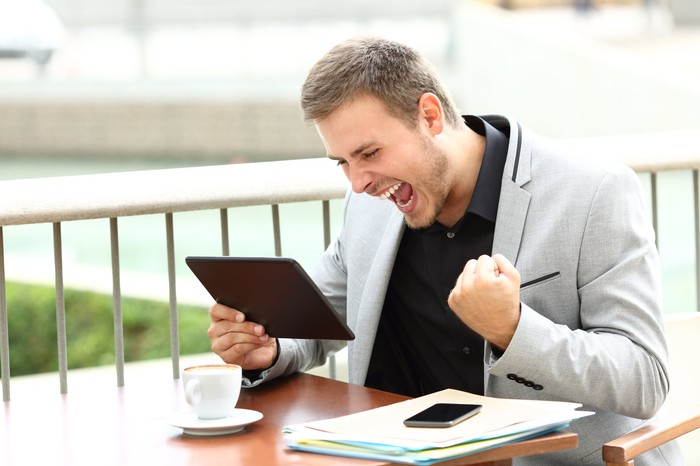 A smiling young businessman shouts and fist-pumps while looking at his tablet.