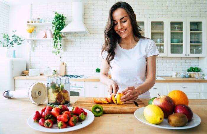 Femme dans une cuisine, couper des fruits pour faire du smoothie.