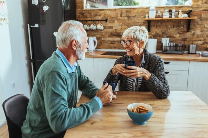 Older couple sitting at kitchen table holding mugs.