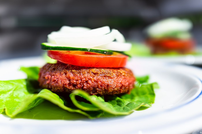 A plant-based burger patty on a bed of lettuce with a tomato and onion on top.