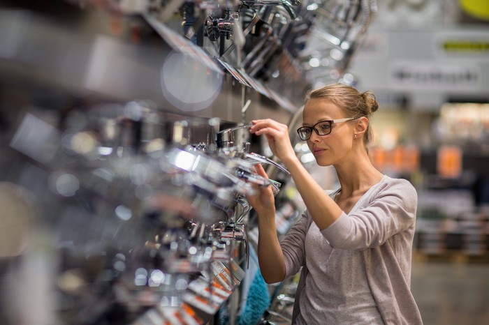 Woman browsing a home goods store like Bed Bath & Beyond, looking at private label merchandise