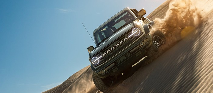 Updated Ford Bronco model driving at a slant on a sand dune.