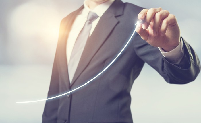 A person in a business suit is drawing an upwardly sloping line.