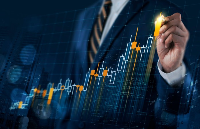 A person in a business suit is pointing to an upwardly sloping stock chart.