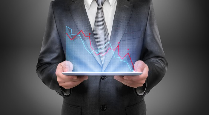 A person in a business suit is holding a tablet displaying downwardly sloping digital charts.
