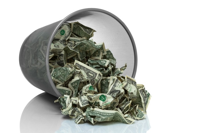 Pile of money in an overturned trashcan.