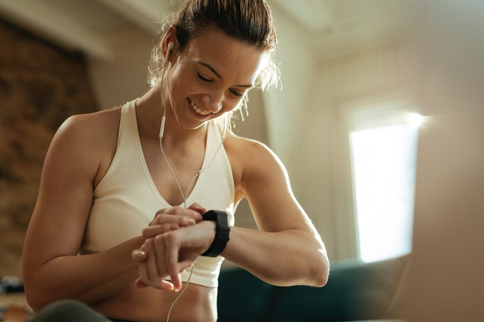 A woman checks her fitness tracker during a workout.