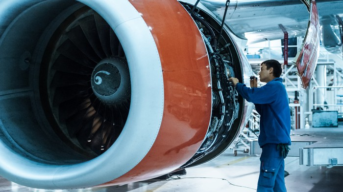 A services engineer working on an aircraft engine.