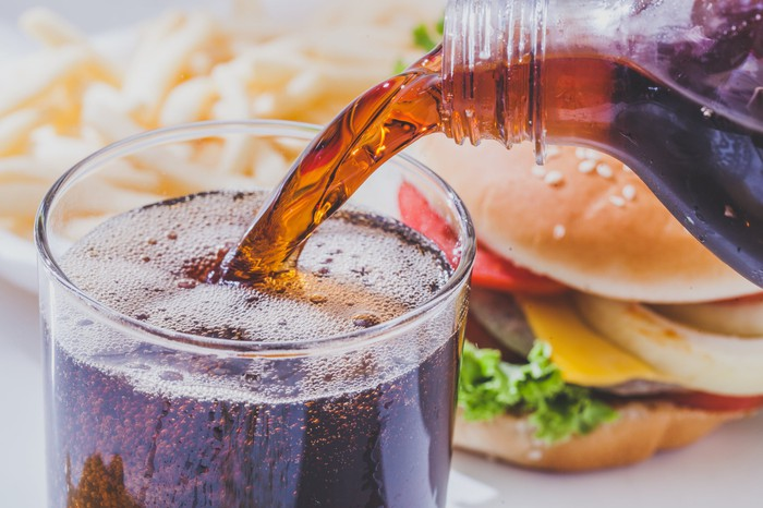 A glass of cola being poured in front of a burger and fries.