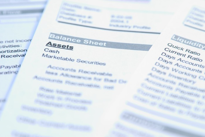 Sheets of paper sit on a table with financial data on them and words like balance sheet, assets, and cash highlighted.
