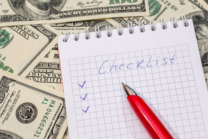 """A pen sits on a notebook with the word """"checklist"""" written on it. The notebook sits atop a pile of money."""