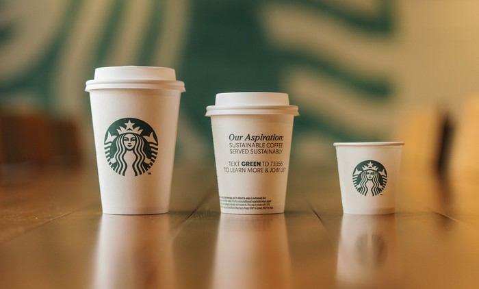 Three paper cups with Starbucks logos.