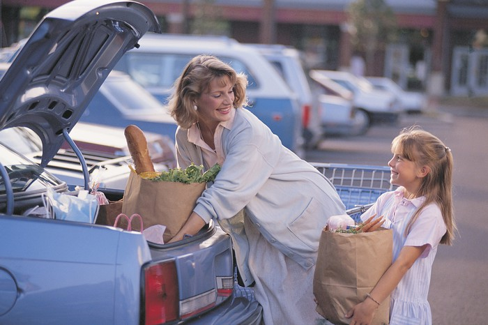 A girl helps a woman putting grocery bags into the trunk of a car